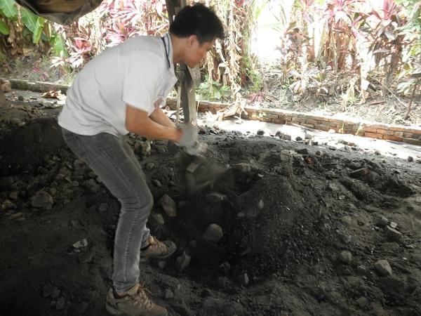 Membuka urukan tanah untuk mengambil masakan